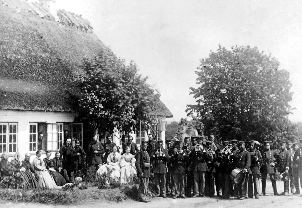 """5. Regiments Musikkorps på Als under våbenhvilen 1864 - identisk med 5. Bataljons musikkorps (se foto fra 1862 senere). 5. og 7. Regiment udgjorde tilsammen 6. Brigade, der bevogtede Als under våbenhvilen. Den høje hornblæser i 2. geled er formentlig Gundelach. Soldaten med gevær ved skulder menes at være genkendt som menig Jens Nissen Hansen Tagmose af 8. Regiment. 5. Regiments musikkorps har igen fået instrumenterne frem. Bagsiden af stereobilledet på Rigsarkivet oplyser: """" Oberst A. C. J Mykrets middag på Als (juni?) 64"""". (Foto: Rigsarkivet)"""