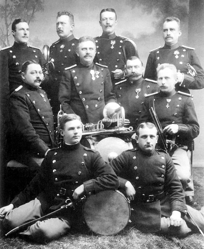 8. Regiments Musikkorps 1913. To værnepligtige siddende på gulvet - 2. række fra venstre: Jensen, Schwartz, Honoré, Ovesen - 3. række fra venstre: Billebølle, Lorentzen, Johnsen, Eckartsen.