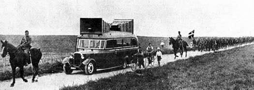Sjældent foto af militær parade, anført af en højttalervogn, der spiller marchmusik - billedet er fra en jubilæums-brochure fra Bagger Radio.